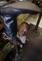 Hiding under a boot, Deyontie Tucker, 1 1/2, looks up as his grandfather's uncle, Richard Tucker works in his Daytona Beach store Tuesday September 17, 2002. He is one of a rare breed of traditional cobblers still in business.(Kelly Jordan)..**FOR CALLEA STORY**