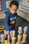 Education Preschool classroom scenes 4-5 year olds boy playing with toy plastic bears and wooden block structure he made