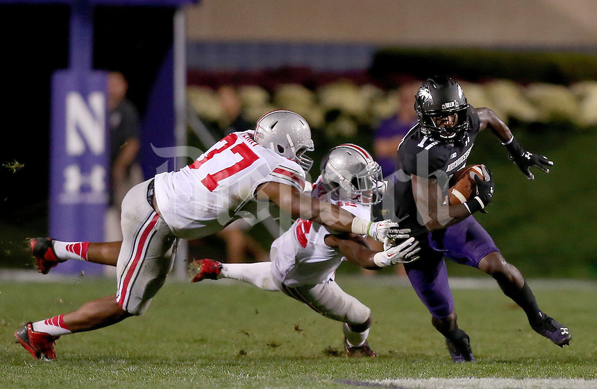 Ohio State Buckeyes linebacker Joshua Perry (37) and Ohio State Buckeyes cornerback Doran Grant (12) tackle Northwestern Wildcats wide receiver Rashad Lawrence (17) during the second half of the NCAA football game between Ohio State and Northwestern at Ryan Field in Evanston, Illinois on Saturday, October 5, 2013. (Columbus Dispatch photo by Jonathan Quilter)