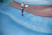 NEW YORK, NY - MAY 27: Artist Jorge Rodríguez looks at the doctor's photograph to continue painting on May 27, 2020 in Queens, New York. The artist Jorge Rodríguez Gerada makes a stunning mural in Flushing Meadows, Corona Park to Dr. Ydelfonso Decoo, an immigrant doctor who died of complications from Coronavirus. The mural is also made in gratitude to the millions of medical workers who have given their lives to fight COVID-19. (Photo by Pablo Monsalve / VIEWpress via Getty Images)
