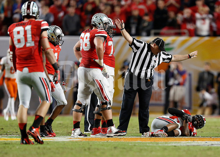 An official calls for an injured Ohio State Buckeyes quarterback Braxton Miller (5) after a hard hit caused an interception in the fourth quarter of the Discover Orange Bowl between Ohio State and Clemson at Sun Life Stadium in Miami Gardens, Florida, Saturday night, January 4, 2014.The Clemson Tigers defeated the Ohio State Buckeyes 40 - 35.(The Columbus Dispatch / Eamon Queeney)