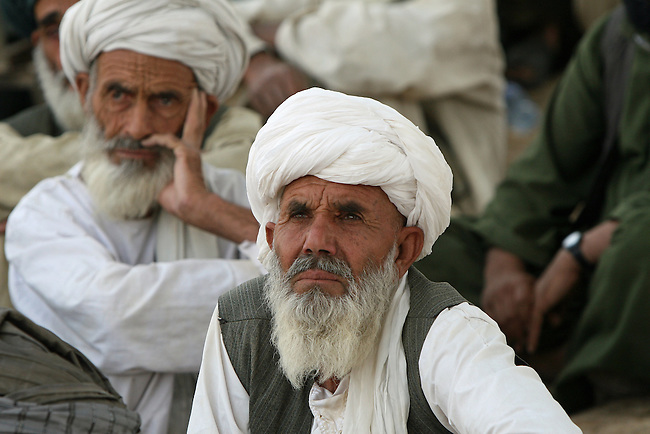 Two men listen as NATO and Afghan military officers urge village elders in Osman Kheyl, in Maiwand district, Afghanistan to cooperate with government and foreign troops in the fight against Taliban insurgents. Taliban attacks have risen sharply across southern Afghanistan in the last two years, and U.S. and other NATO countries are sending more troops to the region. Aug. 7, 2008. DREW BROWN/STARS AND STRIPES