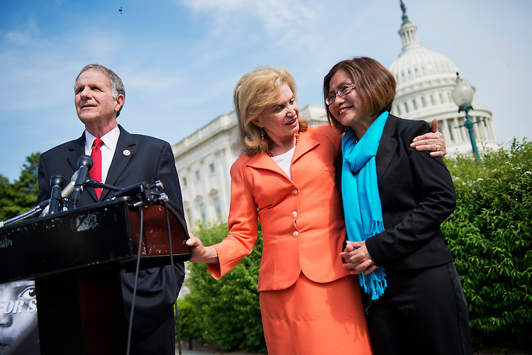 UNITED STATES - MAY 20: Reps. Ted Poe, R-Texas, Carloyn Maloney, D-N.Y., and Shandra Woworuntu, who was a victim of sex trafficking, talk after a news conference, May 20, 2014, at the House Triangle to support the Justice for Victims of Trafficking Act, and the Human Trafficking Fraud Enforcement Act. The legislation would give greater reach to the IRS to go after human traffickers and help support victims. (Photo By Tom Williams/CQ Roll Call)