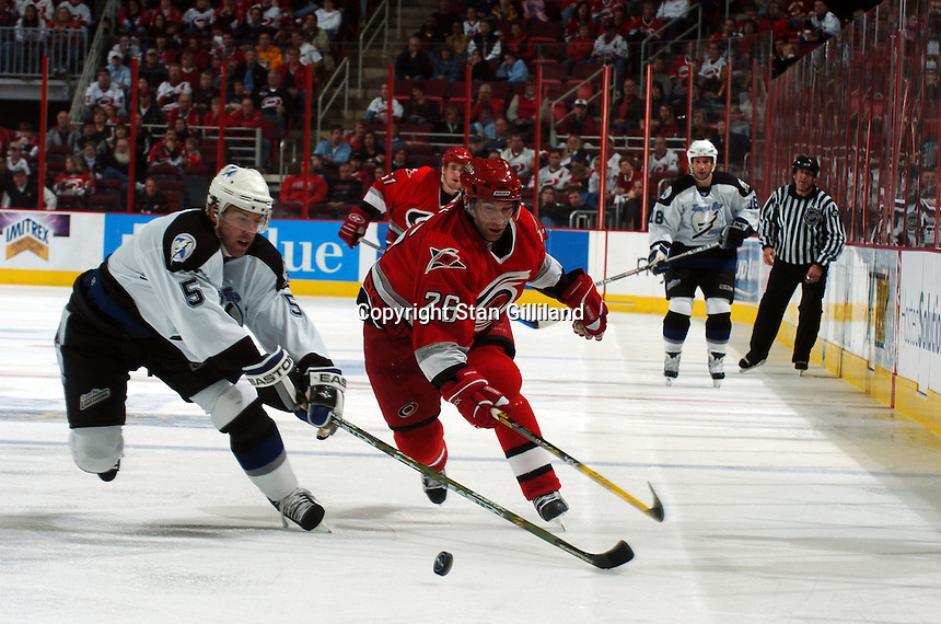 Carolina Hurricanes' Erik Cole (26) vies for a puck with the Tampa Bay Lightning's Darryl Sydor (5) during their game Sunday, Nov. 20, 2005 in Raleigh, NC.  Tampa Bay won 5-2.