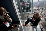 A woman poses for a photo on The Ledge at the Willis Tower Skydeck, Chicago, IL