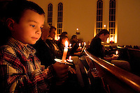 A young boy watches the glowing candle he is holding during a Christmas Eve church service.