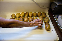 Lida Kaiser prepares potatoes for the Saturday evening guests at the Hamilton Club in Morris Run, PA.