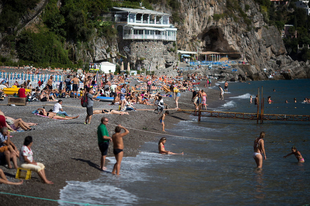 Tourists and sunbathers enjoy a public beach on Sunday, Sept. 20, 2015, in Positano, Italy. (Photo by James Brosher)