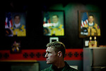 "U2 pilot Maj. Eric Shontz sits at a bar while portraits of pilots who died while flying the U2 line the wall behind him in the U2 pilots' ""Heritage Room"" at Beale Air Force Base February 23, 2010 in Linda, Calif."