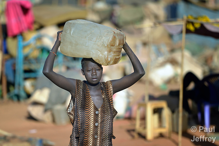 A woman carries water in a camp for over 5,000 internally displaced persons in an Episcopal Church compound in Wau, South Sudan. Most of the families here were displaced by violence early in 2017, after a larger number took refuge in other church sites when widespread armed conflict engulfed Wau in June 2016.<br /> <br /> Norwegian Church Aid, a member of the ACT Alliance, has provided relief supplies to the displaced in Wau, and has supported the South Sudan Council of Churches as it has struggled to mediate the conflict in Wau.