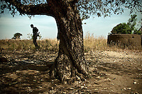 Africa, Sudan, Magwi County, Mugale, Caught In Between, Northern Uganda/Southern Sudan - A Sudanese People's Liberation Army soldier stands near the tree where two victims fell to the ambush of the Lord's Resistance Army. The first, a woman, was shot and injured. The second, a man, was shot and killed. Since the attack the 15,000 inhabitants of Mugale have been making an exodus out of the village towards nearby Nimule. The war in the region began in 1986 between the Lord's Resistance Army and the Ugandan People's Defense Forces (UPDF). The LRA has reigned terror and carnage on Northern Uganda and Southern Sudan ever since. The ongoing conflict has significantly damaged the region and has left an ongoing burden on the local population. December 2005 © Stephen Blake Farrington