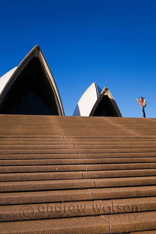 A backpacker photographs the iconic architecture of the Opera House.  Sydney, New South Wales, AUSTRALIA.