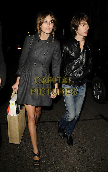 ALEXA CHUNG & ALEX TURNER (ARCTIC MONKEYS).The Universal Music Brit Awards 2009 Afterparty, Claridge's Hotel, Brook St., London, England..February 18th, 2009.brits full length couple grey gray coat jacket black leather jeans denim holding hands burlap bag .CAP/CAN.©Can Nguyen/Capital Pictures.