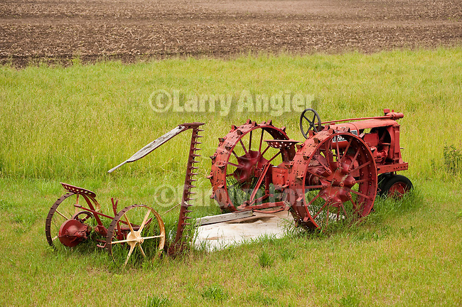 Semi-restored red mid 1930s Farmall F12 tractor with steel wheels and sickle bar mower in a field in rural Indiana