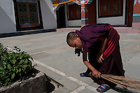 Buddhist Monk performs his duty of sweeping, Monastery in Sikkim, India