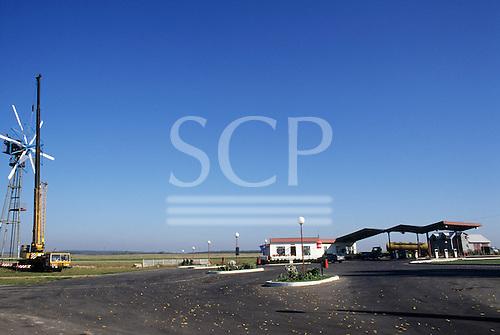Poland. Remote rural petrol filling station; crane installing wind power generator windmill. Near Kracow.