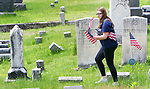 WINSTED CT. 18 May 2018-051818SV04- Shelby Goodell, 21, of Winsted helps her family replace old American Flags with new ones at a cemetery on Oak Street in Winsted Friday. The family replaces the flags at that cemetery every year before Memorial Day.<br /> Steven Valenti Republican-American