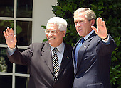 United States President George W. Bush and Prime Minister Mahmoud Abbas of the Palestinian Authority wave to reporters after taking questions on their Oval Office  talks in the Rose Garden of the White House in Washington, D.C. in Washington, DC on July 25, 2003.  After meeting reporters the two leaders retired to lunch in the Residence..Credit: Ron Sachs / CNP