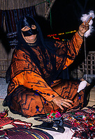 Qurum, Oman.  Middle-aged Masked Woman Spinning Thread from Wool.  Muscat Festival, demonstrating traditional Omani handicrafts.