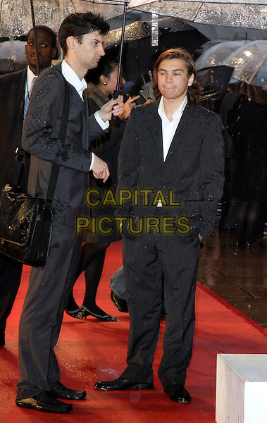 EMILE HIRSCH .Arriving at the Speed Racer - UK film premiere, Empire Leicester Square,.London, England, April 28th 2008..full length black suit raining umbrella funny face.CAP/ROS.©Steve Ross/Capital Pictures