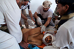 Medics wash the body of a young fighter at a makeshift morgue next to the front-line hospital in Sirte, Libya, Oct. 7, 2011. As revolutionary forces pushed into Sirte to confront pro-Gaddafi forces holed up there, casualties rose, mostly the result of sniper fire, mortar and rocket-propelled grenade injuries. By the end of the day 13 had died and 200 were wounded.