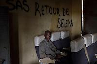 """Ibrahim Toukour, muslimischer Flüchtling in Bangui, Zentralafrikanische Republik, mit seinen Kindern. Die Familie musste vor der Gewalt der überwiegend aus Christen bestehenden Anti-Balaka-Militia flüchten und lebt in einem Lager am Flughafen. Sie hoffen auf die Ausreise nach Kamerun. Im Hintergrund hat jemand """"Sas Retour de Seleka"""" an die Wand geschrieben - die Seleka-Rebellen werden zurückkehren"""