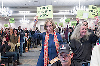 "Diane Turco, of Harwick, Mass., holds a sign reading ""Shut Pilgrim Now"" at a public hearing regarding Pilgrim Station, a nuclear power plant run by Entergy, at Hotel 1620 in Plymouth, Massachusetts, USA, on Tues., Jan. 31, 2017. Turco is the director of the Cape Downwinders, a group of area residents opposing the continued operation of Pilgrim Station. Truco was the recipient of an email from the NRC that was leaked in December 2016 outlining problems with the ""safety culture"" at the plant and an ""overwhelmed"" staff. Area residents have been calling for the plant to be shut down. The green signs in the audience, reading ""Shut Pilgrim Now,"" are from a group of area residents calling for the plant's closure called Cape Downwinders."