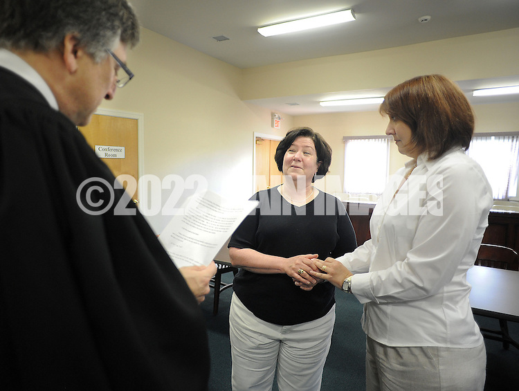 OTTSVILLE, PA - JUNE 17: District Judge Gary Gambardella (L) performs a marriage ceremony for Diane Chronister (C) and Kelly Jennings (R) June 17, 2014 in Ottsville, Pennsylvania. The judge recently announced that he will be holding evening ceremonies in case same-sex couples find it difficult to get married now that the state's ban on same-sex marriage was struck down by a federal court. (Photo by William Thomas Cain/Cain Images)