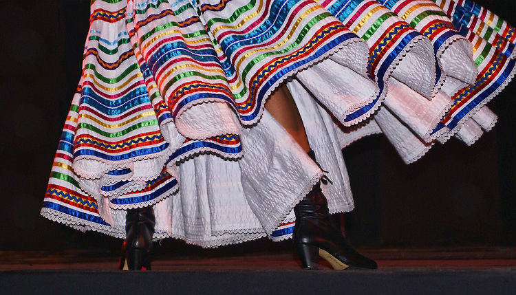 The swinging white skirt, bound by lace and decorated in a rainbow of colorful ribbons, worn by a female dancer preforming Charreada, one of the traditional dances presented by the Ballet Folklorico de Mexico in which female dancers wear colorful costumes that swirl with the movement of the dance. The skirt wraps around the dancer's black boots.