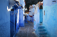 Narrow street in the early morning, with houses and shops painted blue, in the medina or old town of Chefchaouen in the Rif mountains of North West Morocco. Chefchaouen was founded in 1471 by Moulay Ali Ben Moussa Ben Rashid El Alami to house the muslims expelled from Andalusia. It is famous for its blue painted houses, originated by the Jewish community, and is listed by UNESCO under the Intangible Cultural Heritage of Humanity. Picture by Manuel Cohen