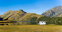 Panoramic Photo of a Caravan Parked at Lake Moke DOC Campsite, Queenstown, South Island, New Zealand. Lake Moke, 10km from Queenstown is both a stunning lake and a department of conservation campsite (DOC campsite) with access for both caravans and campervans. In the early mornings Lake Moke is often perfectly still providing picture perfect reflections of the surrounding hills and mountains in the water. The combination of a fabulous golden hour as the sun rose over the hills, the morning mist lifting from the lake, and the rich, orange, autumn trees made this nights camping at the Lake Moke department of conservation campsite (DOC campsite) particularly special.