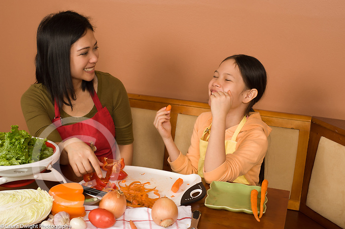 9 year old girl with mother in kitchen talking and laughing food preparation vegetables and salad