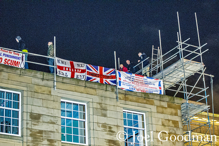 "© Joel Goodman - 07973 332324 . 03/03/2012 . Heywood , UK . Following a National Front demonstration in nearby Heywood, a rooftop demonstration by the ""North West Infidels"" and the ""Combined Ex Forces"" is held on Bury Town Hall. Police said the group had climbed up scaffolding at the side of the Town Hall building to gain roof access. Protesters have affixed banners stating ""Hang paedo scum"" and various nationalist slogans . Photo credit : Joel Goodman"