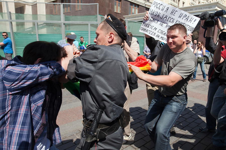 """Moscow, Russia, 28/05/2011..A riot policeman seizes a gay rights demonstrator as a Russian nationalist pulls the demonstrator's flag away and another gay rights activist holds a sign reading """"Russia is not Iran"""". Several dozen people were arrested during clashes as Russian nationalists attacked gay rights activists during their sixth attempt to hold a gay pride parade in the Russian capital."""