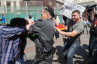 "Moscow, Russia, 28/05/2011..A riot policeman seizes a gay rights demonstrator as a Russian nationalist pulls the demonstrator's flag away and another gay rights activist holds a sign reading ""Russia is not Iran"". Several dozen people were arrested during clashes as Russian nationalists attacked gay rights activists during their sixth attempt to hold a gay pride parade in the Russian capital."
