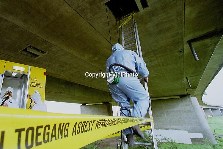 Foto: VidiPhoto..RENKUM - Werknemers van een asbestverwijderingsbedrijf uit Oosterhout .(Gld), klimmen in de holle ruimte van de Rijnbrug (A50) bij Renkum. In vier compartimenten van ieder 1 kilometer lang is bij herstelwerkzaamheden aan de brug asbest aangetroffen. In de holle ruimten is jarenlang zonder beschermende kleding gewerkt door een dertigtal werknemers van diverse aannemers. Volgens hen heeft Rijkswaterstaat bewust de aanwezigheid van asbest verzwegen.