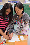 After school enrichment cooking class female teacher volunteering, helping female student with task