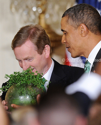 United States President Barack Obama accepts a bowl of shamrocks from Prime Minister Enda Kenny of Ireland during a reception in the East Room of the White House in Washington, D.C., March 19, 2013 in Washington, DC. <br /> Credit: Olivier Douliery / Pool via CNP