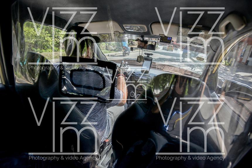 CALI - COLOMBIA, 05-05-2020: Un taxista implementa aislamiento preventivo en su auto como parte de la reactivación economica en la ciudad de Cali durante el día 43 de la cuarentena total en el territorio colombiano causada por la pandemia  del Coronavirus, COVID-19. / A taxidriver implements a preventive isolation in his vehicle as part of the economic revival in Cali City during the day 43 of total quarantine in Colombian territory caused by the Coronavirus pandemic, COVID-19. Photo: VizzorImage / Gabriel Aponte / Staff