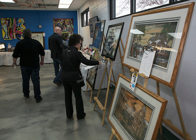 Suejan Sipiora looks at silent auction items during the Jack T. Reviglio Cioppino Feed & Auction at the Donald W. Reynolds Facility in Reno on Saturday, February 25, 2017.