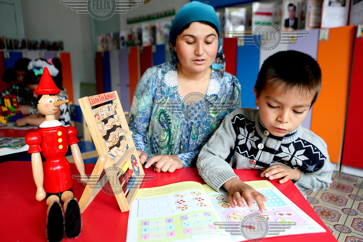 A teacher helps a child with maths at an Early Childhood Education Centre for four to six year olds in Ispisor Jamoat Village.