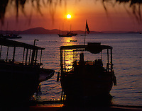 Fishing boats at sunset on the beach at Pattaya in Thailand.
