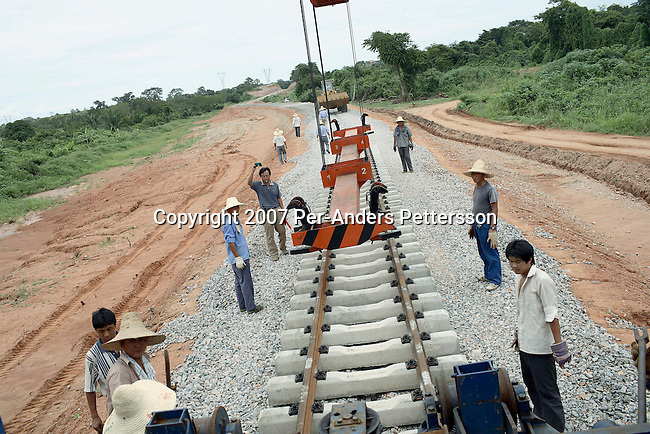 DONDO, ANGOLA APRIL 4: Chinese railway workers put tracks on April 4, 2007 in Dondo, about 200 kilometers outside Luanda, Angola. Chinese companies are building and upgrading two different railways in Angola, and this part is about 500 kilometers long. All the special equipment has been shipped from China and hundreds of workers live in military style road camps. They are moved as the tracks are laid down. Tens of thousands of Chinese has come to Africa the last years to work in infrastructure projects and businesses. Chinese companies are often the lowest bidders for contracts, pricing out the more expensive European companies. The Chinese people often live where they work and rarely interact with the local population. Most Chinese don't speak English and they are mostly staying in the compounds cooking their Chinese food. (Photo by Per-Anders Pettersson)....