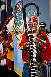 A Navajo Code Talker holds a sacred staff as he leads the honor guard.