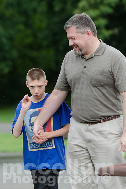 """Michael McCollum<br /> 8/2/18<br /> David Overman arrives with his son Ryan,13,at the reveal ceremony where it was announced to Ryan Overman of west Knoxville that The Wish Connection is granting Ryan's wish to go to Washington DC and visit the White House at Carl Cowan Park, 10058 S Northshore Dr, Knoxville, TN, Thursday, August 2, 2018 at 5:45pm. Approximately 50-60 people attended, including the Overman family, friends, and AT&T Employees. The Bearden High School Cadets also attended and lead the pledge of allegiance.<br /> The AT&T Wish Connection is going to send Ryan, his family, and his service dog to Washington DC and while they are gone, the group of volunteers will be doing a makeover on his bedroom and turn it into the """"Oval Office"""" at the White House.<br /> Ryan was born two weeks prematurely on May 13, 2005. During the pregnancy he was classified as high risk due to a measured lack of growth and, after a brief stay in the hospital, he came home weighing only 4 lbs 5 oz. His development was much slower compared to his peers, such as not learning to walk until he was well over a year old, and he was much smaller. The Overman family worked with Tennessee Early Intervention Services (TEIS) when Ryan was about one year old and with their help they were able to get Ryan enrolled through TEIS to receive Occupational, Physical, and Speech Therapy. When Ryan turned three he transitioned from TEIS to the Knox County Early Intervention Program and began attending a special school to continue his therapies until he was old enough to enroll at Cedar Bluff Elementary and now is at Cedar Bluff Middle School. In 2016, Ryan was diagnosed to have retinitis pigmentosa, a degenerative disease of the retinas that under the best of circumstances causes severe tunnel vision, but more commonly results in complete blindness.<br /> Despite the physical difficulties that Ryan has had to endure over the last thirteen years, he continually brightens the lives of those around him. I"""