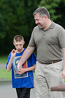 Michael McCollum<br /> 8/2/18<br /> David Overman arrives with his son Ryan,13,at the reveal ceremony where it was announced to Ryan Overman of west Knoxville that The Wish Connection is granting Ryan&rsquo;s wish to go to Washington DC and visit the White House at Carl Cowan Park, 10058 S Northshore Dr, Knoxville, TN&nbsp;, Thursday, August 2, 2018 at 5:45pm. Approximately 50-60 people attended, including the Overman family, friends, and AT&amp;T Employees. The Bearden High School Cadets also attended and lead the pledge of allegiance.<br /> &nbsp;The AT&amp;T Wish Connection is going to send Ryan, his family, and his service dog to Washington DC and while they are gone, the group of volunteers will be doing a makeover on his bedroom and turn it into the &quot;Oval Office&quot; at the White House.<br /> Ryan was born two weeks prematurely on May 13, 2005.&nbsp; During the pregnancy he was classified as high risk due to a measured lack of growth and, after a brief stay in the hospital, he came home weighing only 4 lbs 5 oz.&nbsp; His development was much slower compared to his peers, such as not learning to walk until he was well over a year old, and he was much smaller. The Overman family worked with Tennessee Early Intervention Services (TEIS) when Ryan was about one year old and with their help they were able to get Ryan enrolled through TEIS to receive Occupational, Physical, and Speech Therapy.&nbsp; When Ryan turned three he transitioned from TEIS to the Knox County Early Intervention Program and began attending a special school to continue his therapies until he was old enough to enroll at Cedar Bluff Elementary and now is at Cedar Bluff Middle School. In 2016, Ryan was diagnosed to have retinitis pigmentosa, a degenerative disease of the retinas that under the best of circumstances causes severe tunnel vision, but more commonly results in complete blindness.<br /> &nbsp;Despite the physical difficulties that Ryan has had to endure over the last thirteen years, he continually brightens the lives of those around him.&nbsp; If someone is h