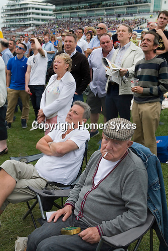 The Derby horse race. Epsom Down Surrey UK. Father and son working class father wearing cloth cap and smoking a roll your own. Grandstand in background. Watching the horse racing on broadcast event screen.