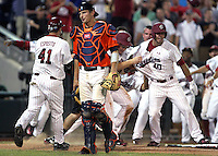 Virginia catcher John Hicks walks away as South Carolina's Adam Matthews (26) scores the winning run and is greeted by teammate Jake Williams (40) in the 13th inning. South Carolina advanced to the Championship Series of the College World Series with a 3-2 win on June 24, 2011 in Omaha, Neb. (Photo by Michelle Bishop)..