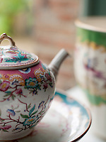 A close up of a delicate tea pot decorated with a floral pattern.