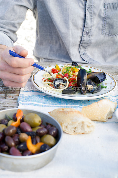 Closeup of a man's torso and hand, eating a plate of mussels and linguine at a picnic table. Bread and bowl of olives in the foreground.